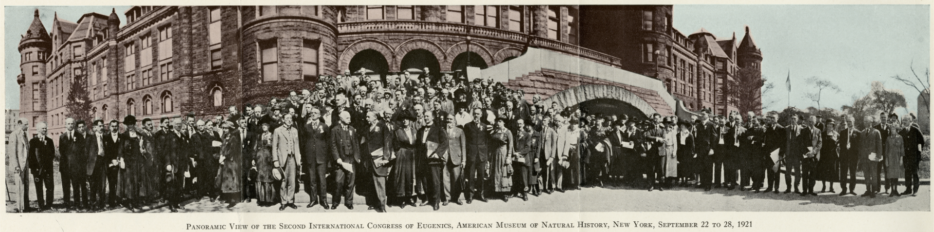 """A partially colorized panoramic photo of participants of the Second International Congress of Eugenics posing in front of the American Museum of Natural History building. In the picture, the building is colorized in light brown shade and the participants are in black and white. There are 151 people in the photo whom are mostly men with some women also visible. All participants are well-dressed in the fashion of that era. The caption of the photo reads """"Panramic View of the Second International Congress of Eugenics, American Museum of Natural History, New York, September 22 to 28, 2921""""."""